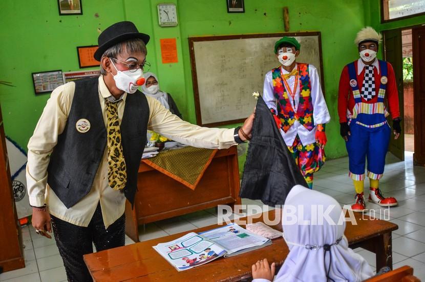 Komunitas Badut Tasikmalaya (Battik) menyanyikan lagu 3M saat sosialisasi protokol kesehatan pada pembelajaran tatap muka SD Negeri Dadaha, Kota Tasikmalaya, Jawa Barat, Senin (27/9/2021). Komunitas Badut Tasikmalaya melakukan edukasi protokol kesehatan dengan aktraksi dan permainan interaktif serta membagikan masker guna mencegah penyebaran COVID-19 serta meminimalisasi klaster baru di lingkungan sekolah saat pembelajaran tatap muka terbatas.