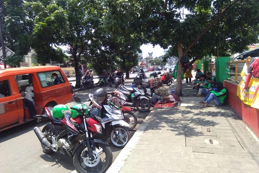 Kondisi bahu jalan di depan Mall Tamini Square, Jakarta Timur terlihat seperti parkir liar. Hal ini disebabkan oleh banyaknya kendaraan bermotor yang parkir di bahu jalan tersebut.  Kebanyakan dari mereka yang memarkir di bahu jalan ini adalah para pengemudi ojek online.