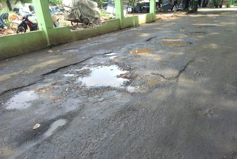 Kondisi jalan di pintu masuk Gelanggang Olahraga (GOR) Bekasi, Kota Bekasi rusak parah.