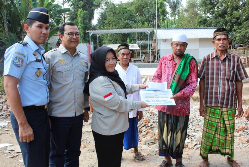 Konsul Imigrasi KJRI Johor Bahru I Gusti M Ibrahim (kiri) menyerahkan bantuan pembangunan Mushala Ar Rahmah yang rusak akibat gempa di Dusun Montong Dao, Desa Teratak, Kecamatan Batukliang Utara, Lombok Tengah, Rabu (10/10) kemarin.