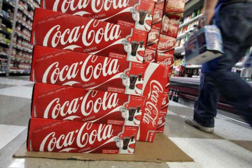 Konsumen berjalan melewati kardus produk Coca Cola di Palo Alto, California.