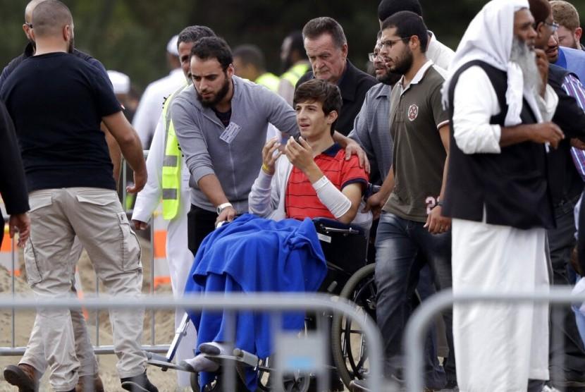 Korban selamat penembakan di Masjid Christchurch, Zaed Mustafa (di kursi roda) saat berada di pemakaman adiknya Hamza dan ayahnya Khalid Mustafa di Memorial Park Cemetery, Christchurch, Selandia Baru, Rabu (20/3).