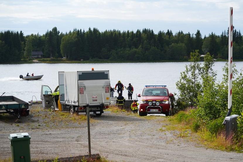 Layanan darurat dengan bagian-bagian reruntuhan pesawat tiba di sebuah pelabuhan kecil dekat lokasi kecelakaan di sungai Ume di luar Umea, Swedia, 14 Juli 2019. Menurut laporan, sebuah pesawat olahraga kecil dengan sembilan orang di dalamnya telah jatuh menewaskan semuanya.