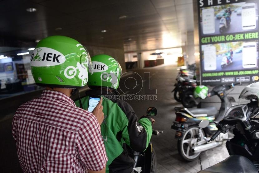 Layanan ojek motor berbasis aplikasi, Gojek, membawa penumpangnya.