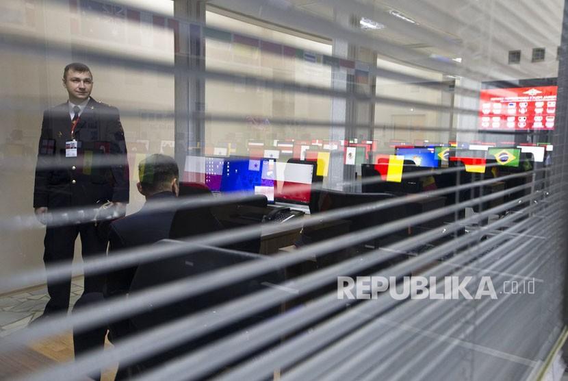 Layar komputer yang menunjukkan bendera nasional dari negara-negara yang berpartisipasi dalam Piala Dunia 2018 tercermin dalam dinding kaca ketika seorang perwira polisi Rusia memeriksa, di Pusat Kerjasama Polisi Internasional dibuka di Domodedovo, di luar Moskow, Rusia, Selasa (12/6).