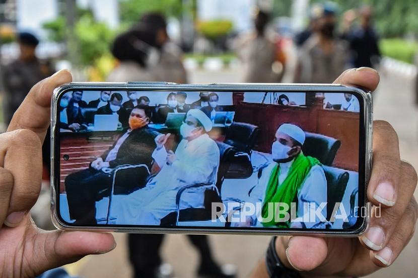 Layar telepon pintar menampilkan suasana sidang Habib Rizieq Shihab (tengah).