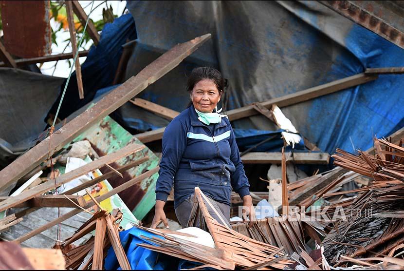 Layla berpose di depan rumahnya yang rusak akibat gempa dan tsunami di Lere, Palu, Sulawesi Tengah.