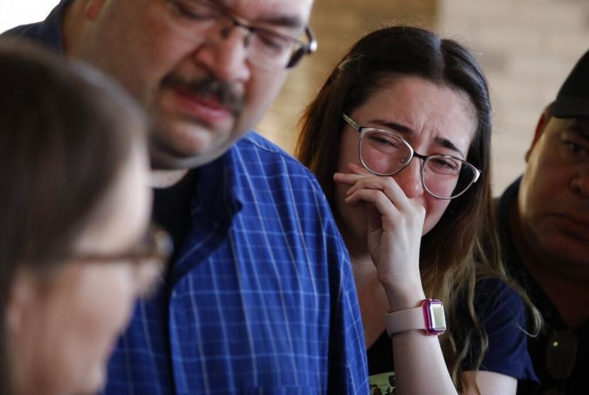 Leta Jamrowski mengusap air matanya saat orang tuanya Misti Jamrowski (kiri) dan Paul Jamrowski berbicara kepada media di University Medical Center, El Paso, Texas, Ahad (4/8). Saudara perempuan Leta meninggal dalam penembakan di kompleks perbelanjaan El Paso.