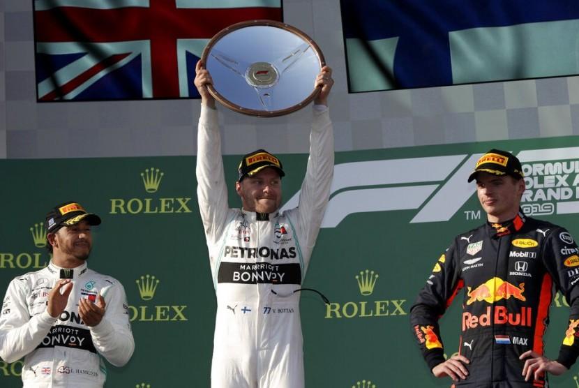 Lewis Hamilton (kiri) menyaksikan Valtteri Bottas mengangkat trofi juara GP Australia 2019.
