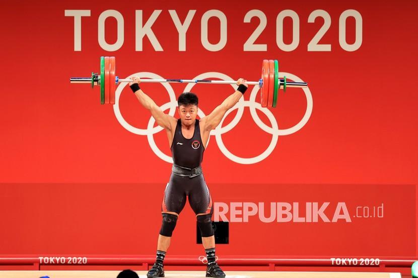 Lifter Indonesia Rahmat Erwin Abdullah melakukan angkatan snatch dalam kelas 73 kg Putra Grup B Olimpiade Tokyo 2020 di Tokyo International Forum, Tokyo, Jepang, Rabu (28/7/2021). Rahmat Erwin Abdullah berhasil meraih medali perunggu dengan total angkatan 342 kg.