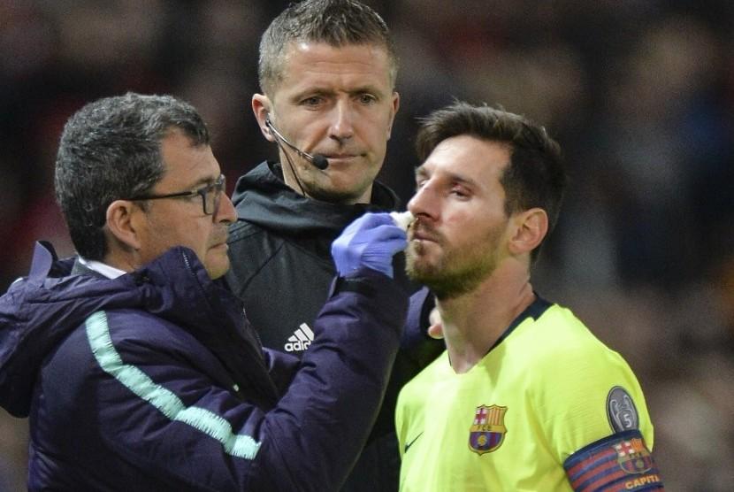 Lionel Messi (kanan) mendapatkan perawatan dokter dalam laga Manchester United vs Barcelona.