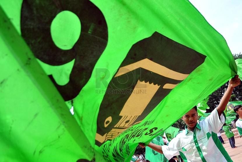 Simpatisan mengibarkan bendera Partai Persatuan Pembangunan (PPP) saat kampanye PPP Tugu Proklamasi, Jakarta Pusat, Sabtu (5/4). (Republika/Prayogi)