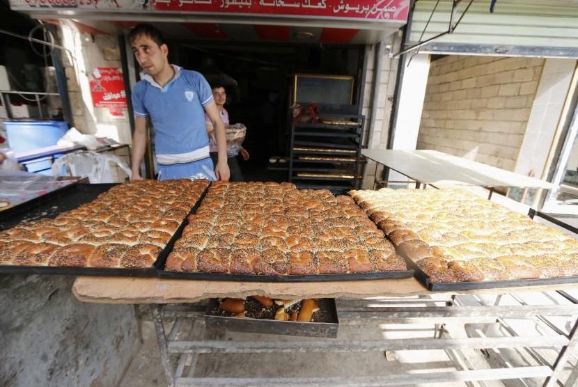 Seorang pria menjual roti manis di hari pertama bulan suci Ramadhan di kota Aleppo, Suriah.   (Reuters/Hosam Katan Al-Fardous)