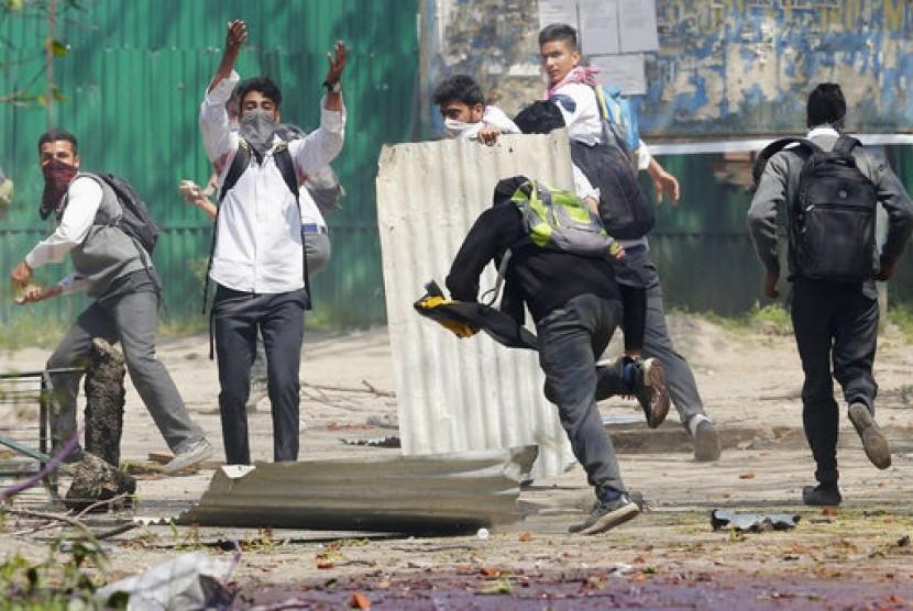 Mahasiswa Kashmir berlari mencari perlindungan saat polisi India menembakkan peluru karet dan gas air mata untuk membubarkan bentrokan di Srinagar, Kashmir yang dikuasai India.