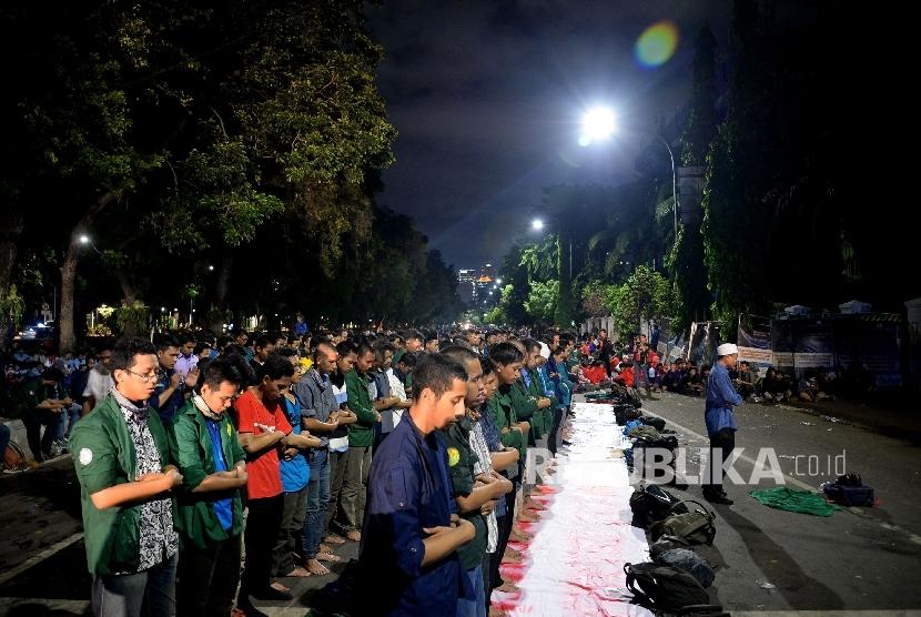 Sejumlah mahasiswa yang tegabung dalam aliansi BEM Se-Indonesia melakukan Sholat Isya saat aksi bela rakyat 121 di depan Istana Merdeka, Jakarta,Kamis (12/1).
