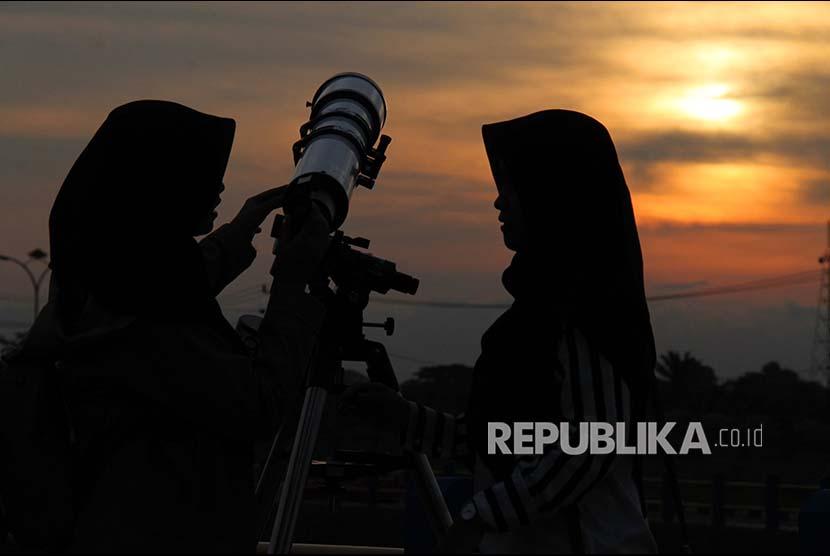 Mahasiswi memantau penampakan hilal untuk menentukan 1 Ramadhan tahun ini melalui alat teropong di Kampus ITERA Lampung,Selasa (15/5). Meski hilal tak tampak karena tertutup awan, mahasiswa tetap antusias mengikuti pelajaran ini.