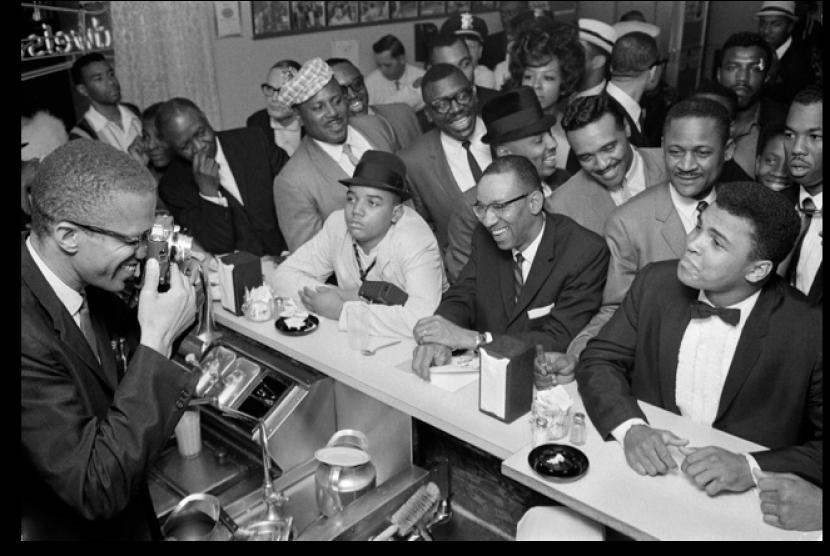 Malcolm X tampak sedang memotret Muhammad Ali