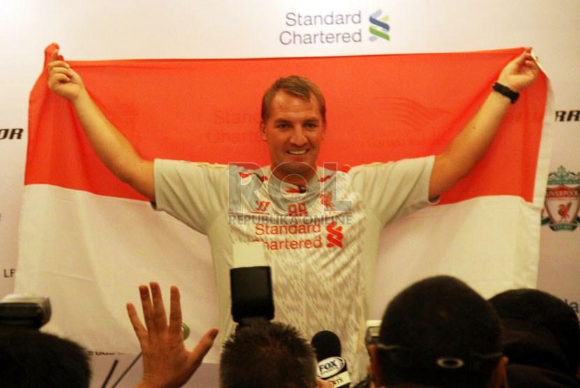 Manajer Liverpool, Brendan Rodgers, mengangkat bendera Indonesia saat konferensi pers di Jakarta, Kamis (18/7).
