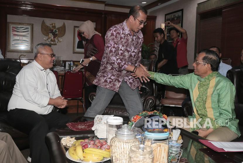 Mantan Ketua Mahkamah Konstitusi Mahfud MD (kanan) berjabat tangan dengan Anggota KPU Hasyim Asyari (tengah) disaksikan oleh Ketua KPU Arief Budiman (kiri) saat tiba di Gedung KPU, Jakarta, Senin (3/12/2018).