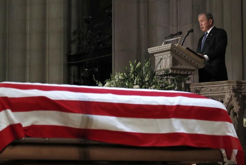 Mantan Presiden George W. Bush terdiam sesaat ketika berbicara di depan peti mati ayahnya, mantan Presiden George H.W. Bush, dalam prosesi Penguburan Kenegaraan di National Cathedral, di Washington, Rabu (5/12).