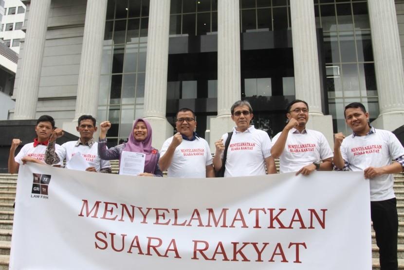 Mantan Wakil Menkum HAM, Denny Indrayana (tengah) bersama Penelitii utama NETGRIT, Hadar Nafis Gumay (ketiga kanan) dan Direktur PERLUDEM, Titi Anggraini (ketiga kiri) dan sejumlah aktivis Pemilu membentangkan spanduk usai mendaftarkan uji materi UU Nomor 7 Tahun 2017 tentang Pemilu, terutama yang terkait dengan syarat prosedur administratif di Gedung Mahkamah Konstitusi, Jakarta, Selasa (5/3/2019).