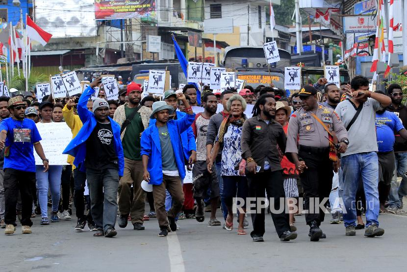 Massa berjalan kaki menuju Kantor Gubernur Papua saat melakukan aksi di Jayapura, Senin (19/8). Aksi tersebut untuk menyikapi peristiwa yang dialami mahasiswa asal Papua di Surabaya, Malang dan Semarang.