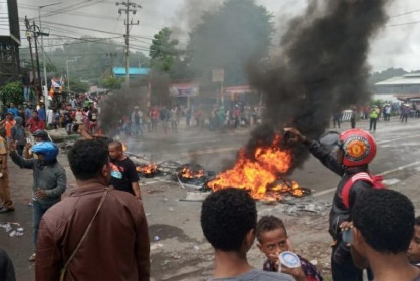 Massa membakar ban saat kerusuhan di pintu masuk Jl. Trikora Wosi Manokwari, Senin (19/8/2019). Aksi ini merupakan buntut dari kemarahan mereka atas peristiwa yang dialami mahasiswa asal Papua di Surabaya, Malang, dan Semarang.