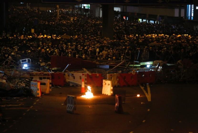 Massa penentang aturan ekstradisi berkumpul di belakang barikade di dekat kantor Dewan Legislatif di Hong Kong, Rabu malam (12/6).