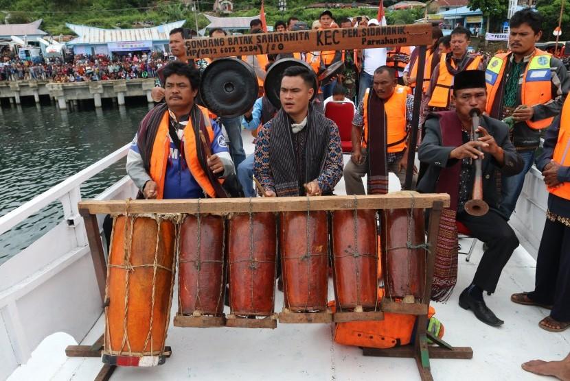 Masyarakat adat Batak memainkan alat musik Gondang ketika melaksanakan ritual di atas kapal motor, di Danau Toba, Simalungun, Sumatera Utara, Sabtu (23/6).