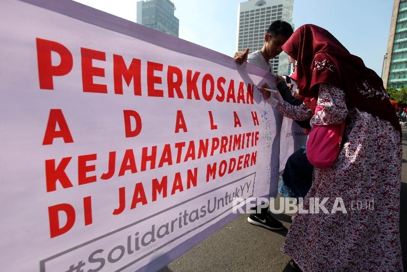 Masyarakat membubuhkan tanda tangannya di spanduk sepanjang 300 meter pada aksi solidaritas untuk YY, korban pelecehan seksual di Bengkulu pada Hari Bebas Kendaraan Bermotor, Jakarta Pusat, Ahad (8/5). (Republika/Rakhmawaty La'lang)