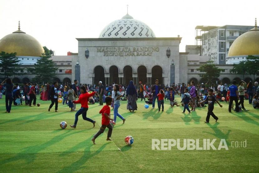Masyarakat menikmati suasana sore hari saat ngabuburit, di Alun-alun, Kota Bandung, Ahad (4/6).