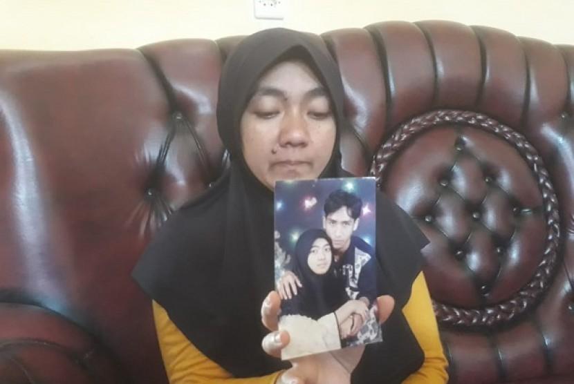 Meli Rahmawati (33), warga Kampung Ciodeng Timur, Desa Bojong Malaka, Kecamatan Baleendah, Kabupaten Bandung tengah menunjukan foto suaminya, Ujang Nuryanto (37) yang diduga menjadi korban mutilasi di Malaysia, Senin (11/2).