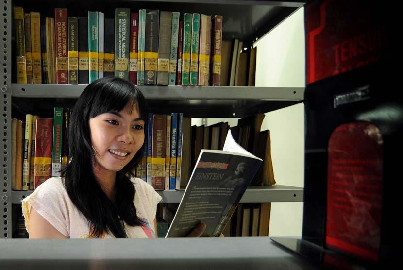 Membaca buku di perpustakaan (ilustrasi).