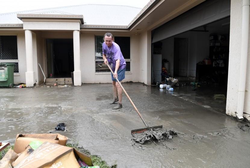 Membersihkan rumah setelah banjir.