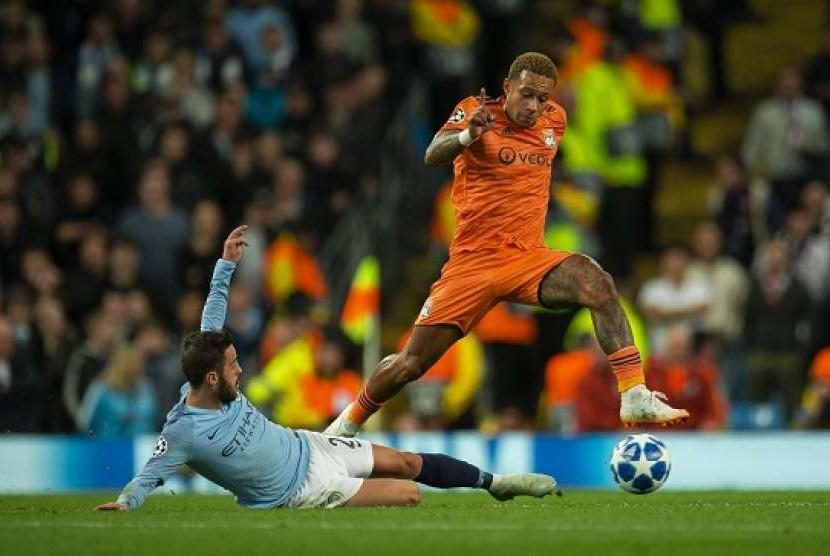 Memphis Depay (kanan) saat membela Lyon melawan Manchester City.