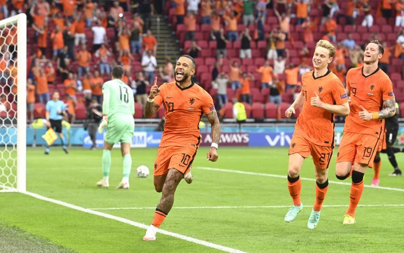 Memphis Depay (tengah) dari Belanda merayakan gol pembuka dari titik penalti pada pertandingan sepak bola babak penyisihan grup C UEFA EURO 2020 antara Belanda dan Austria di Amsterdam, Belanda, Kamis (17/6)..