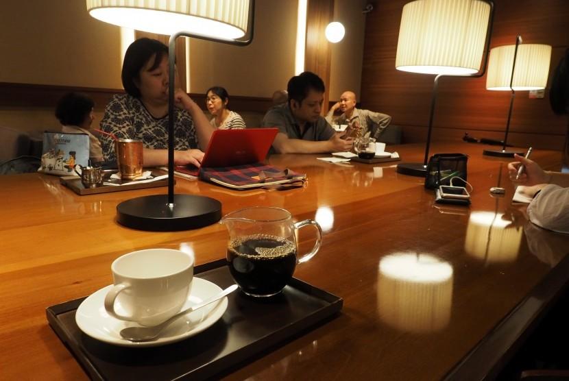 Menikmati kopi di kafe.