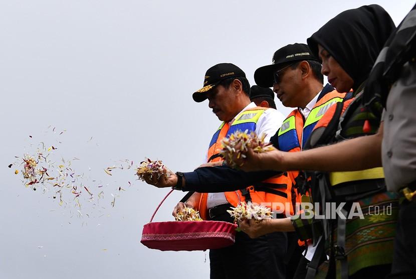 Menko Kemaritiman Luhut Binsar Pandjaitan (kiri) didampingi mantan Wakil Gubernur Sumut Nurhajizah Marpaung (kanan) dan Bupati Simalungun JR Saragih (tengah) menabur bunga untuk korban tenggelamnya KM Sinar Bangun di Danau Toba, Sumatra Utara, Senin (2/7).