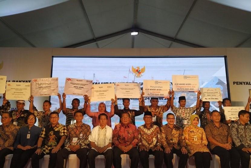 Menko Perekonomian Darmin Nasution berfoto bersama para penerima Kredit Usaha Rakyat (KUR) Perikanan Rakyat di Demak, Jawa Tengah, Ahad (24/3).