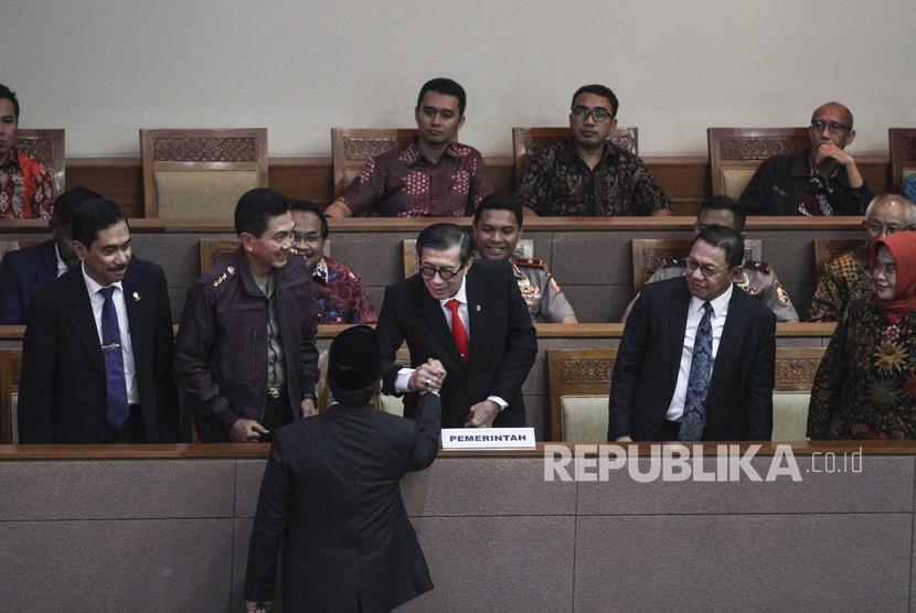 Menkumham Yasonna Laoly (tengah) berjabat tangan dengan Ketua Pansus RUU Anti-Terorisme Muhammad Syafii disaksikan Kepala BNPT Komjen Pol Suhardi Alius (kiri), Irwasum Polri Komjen Pol Putut Eko Bayuseno (kedua kiri), Jampidum Noor Rachmad (kedua kanan) dan Ketua Tim Panitia Kerja Pemerintah untuk RUU Anti-Terorisme Enny Nurbaningsih (kanan) pada Rapat Paripurna di Kompleks Parlemen Senayan, Jakarta, Jumat (25/5).