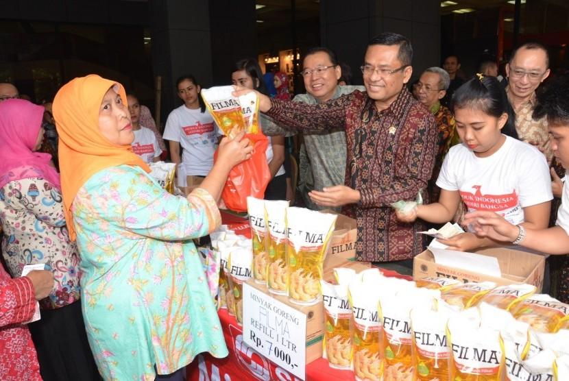 Menperin Saleh Husin (tengah) melayani pembeli minyak goreng pada Bazar Lebaran Tahun 2016 di Plasa Pameran Industri Kementerian Perindustrian, Jakarta, Selasa (21/6).