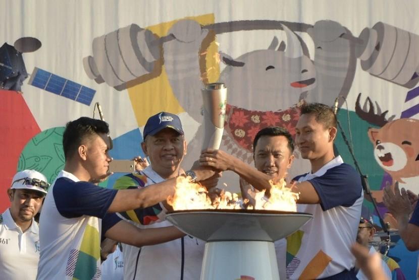 Menpora Imam Nahrawi (kedua kanan), Ketua DPR Bambang Soesatyo (kedua kiri), Pebulu tangkis Sony Dwi Kuncoro (kanan) dan penulis Arief Muhammad menyulut api obor saat pawai obor (torch relay) Asian Games 2018 di kawasan Garuda Wisnu Kencana (GWK), Badung, Bali, Selasa (24/7).