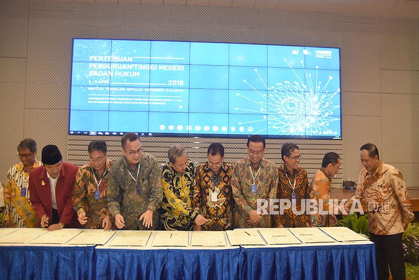 Menristekdikti Mohamad Nasir (kanan) menyaksikan sejumlah Rektor Perguruan Tinggi Negeri menandatangani nota kesepahaman di sela-sela Pertemuan Perguruan Tinggi Negeri Badan Hukum (PTN-BH) 2018 di Gedung Pusat Riset Institut Teknologi Sepuluh November (ITS), Surabaya, Jawa Timur, Rabu (4/4).