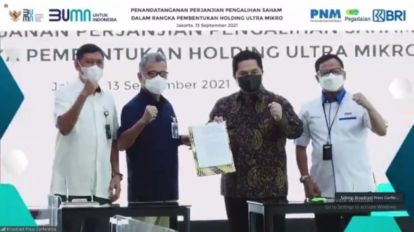 Menteri BUMN Erick Thohir (kedua dari kanan), Dirut Pegadaian Kuswiyoto (kiri), Dirut BRI Sunarso (kedua dari kiri), dan Dirut PNM Arief Mulyadi (kanan) saat penandatangan perjanjian pengalihan saham dalam rangka pembentukan Holding Ultramikro di Jakarta, Senin (13/9).