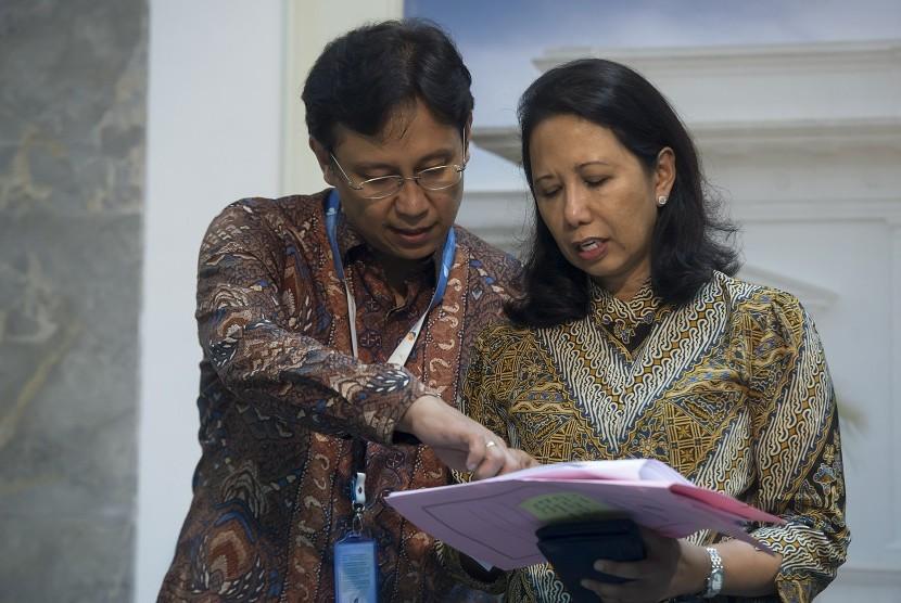 Menteri BUMN Rini Soemarno (kanan) berbincang dengan staf khususnya Budi Gunadi Sadikin (kiri) sebelum memberikan keterangan pers hasil rapat kabinet terbatas di Kantor Kepresidenan, Jakarta, Jumat (12/8).