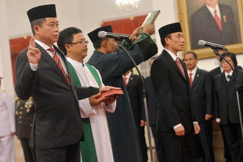 Menteri ESDM Ignasius Jonan (kiri) dan Wamen ESDM Arcandra Tahar (kanan) mengucapkan sumpah jabatan saat upacara pelantikan yang dipimpin Presiden Joko Widodo di Istana Negara, Jakarta, Jumat (14/10).