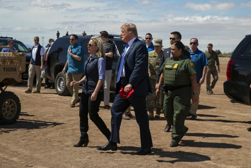 Menteri Keamanan Dalam Negeri AS Kirstjen Nielsen mendampingin Presiden AS Donald Trump saat mengunjungi sebagian tembok perbatasan dengan Meksiko di Calexico, Kalifornia, Jumat (5/4).