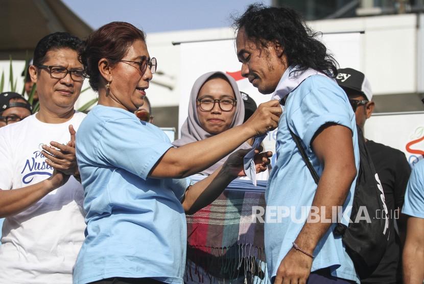 Menteri Kelautan dan Perikanan Susi Pudjiastuti menyematkan syal kepada musisi grup band Slank Kaka (kanan) saat meresmikan Pandu Laut Nusantara di kawasan Bundaran HI, Jakarta, Minggu (15/7).
