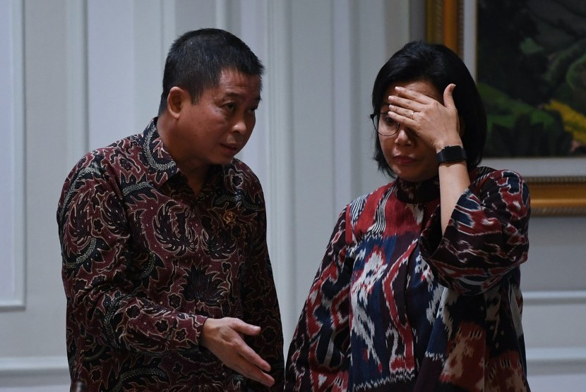 Menteri Keuangan Sri Mulyani (kanan) berbincang dengan Menteri ESDM Ignasius Jonan sebelum mengikuti rapat kabinet terbatas di Kantor Presiden Jakarta, Senin (15/7/2019).