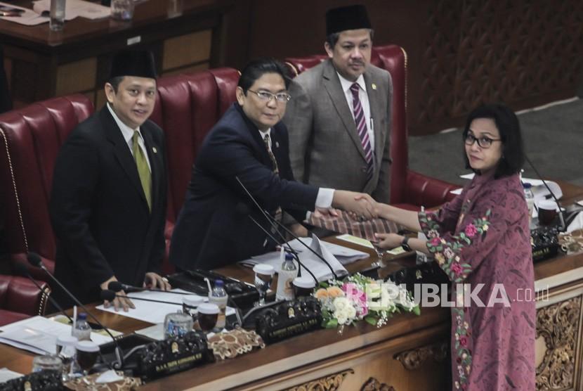 Menteri Keuangan Sri Mulyani (kanan) memberikan hasil tanggapan pemerintah kepada Ketua Sidang Utut Adianto (kedua kiri), disaksikan Ketua DPR Bambang Soesatyo (kiri) dan Wakil Ketua DPR Fahri Hamzah pada Sidang Paripurna DPR di Komplek DPR, Jakarta, Selasa (17/7).